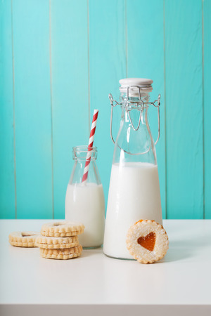 Old fashion milk jars with heart shaped cookies on pastel blue background Banco de Imagens