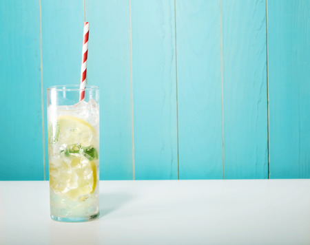 Iced lemonade with big red striped straws on pastel blue background