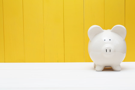 White piggy bank against a yellow wooden wall Stockfoto