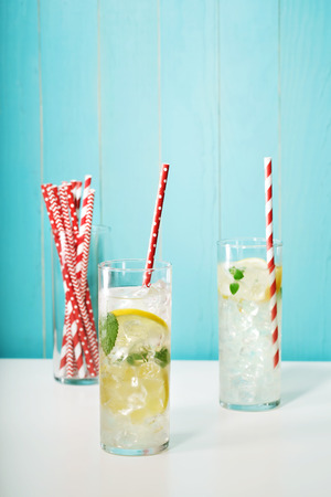water bottle: Homemade lemonades with assorted big red paper straws on pastel blue background