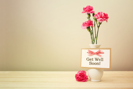 Get well soon message with pink carnations in a white vase Foto de archivo