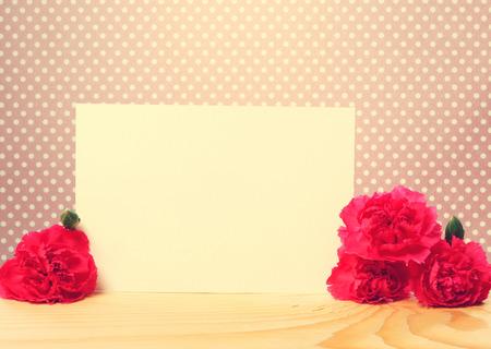 trompo de madera: Tarjeta de felicitación con Flores del clavel en la cima de una tabla de madera con lunares rosados ??del fondo