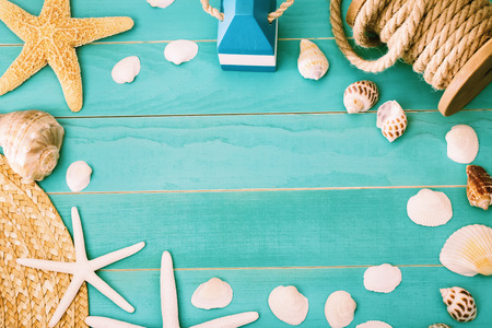 shell: Sea shells and straw hat on light blue wooden background