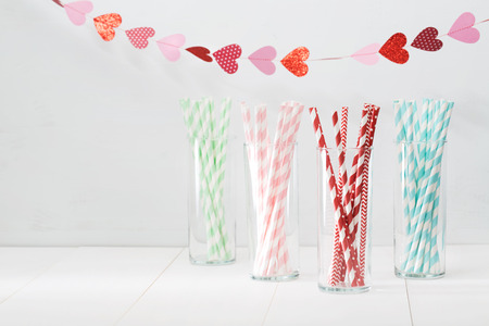 Colorful paper straws with a decorative garland of hearts symbolic of love to celebrate a party for a festive romantic occasion, with copyspace for your invitation or greeting Standard-Bild