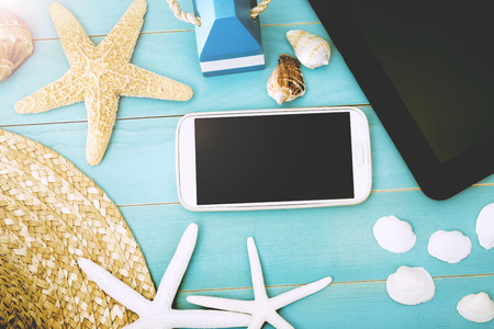 top angle: High Angle View of Mobile Gadgets on Top of Light Blue Table with Starfish, Sea Shells and Beach Hat Stock Photo