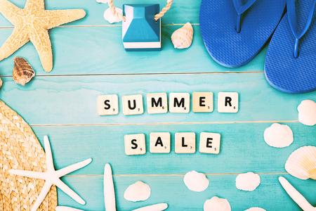 바다 쉘, 불가사리, 비치 모자와 여름 판매 개념에 대 한 슬리퍼와 라이트 블루 테이블에 나무 블록