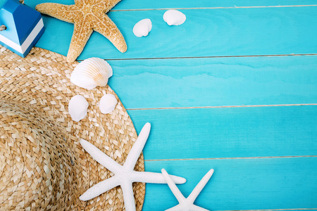 High Angle View of Beach Hat, Sea Shells and Starfish on Top of Light Cool Blue Table with Copy Space for Texts. Stock Photo
