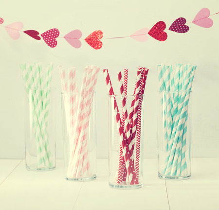 straws: Colorful paper straws with a decorative garland of hearts symbolic of love to celebrate a party for a festive romantic occasion