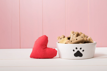 treat like a dog: I Love My Dog concept with a red textile heart alongside a doggy bowl decorated with a paw print and filled with biscuits, pink background with copyspace Stock Photo