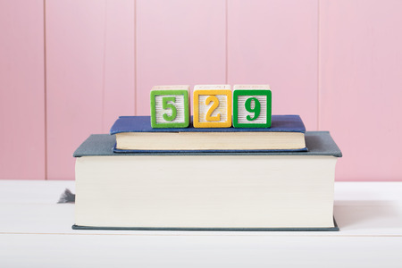 college fund savings: 529 college savings plan concept with textbooks stacked in front of a pink wooden background with copyspace