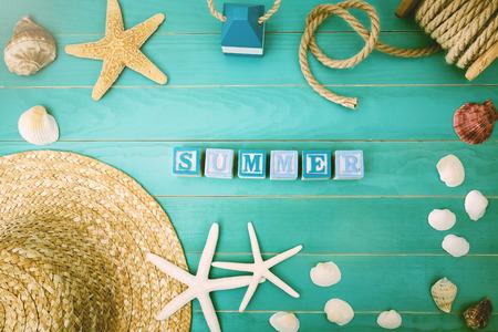 高角度的蓝色木块在浅蓝色桌子与什锦贝壳和海星夏季概念
