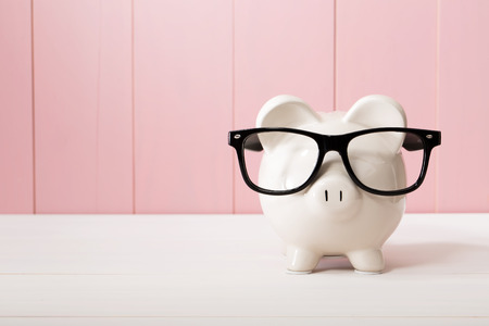 Piggy bank with black glasses on pink wooden wall Foto de archivo