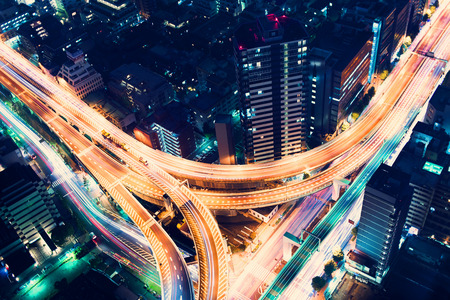 Aerial view of a massive highway intersection at night in Shinjuku, Tokyo, Japan