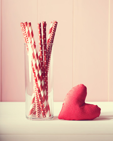 red paper: Romantic Valentines Day greeting card design with a handcrafted red heart and glass full of colorful red and white straws against a rustic pink wooden wall