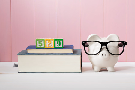 529 college savings and paying for education concept with piggy bank wearing eyeglasses alongside textbooks
