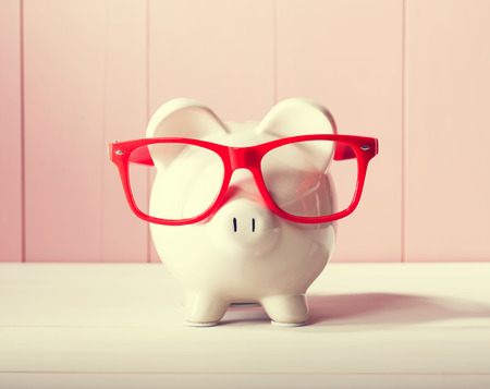 Piggy bank with red glasses on pink wooden wall