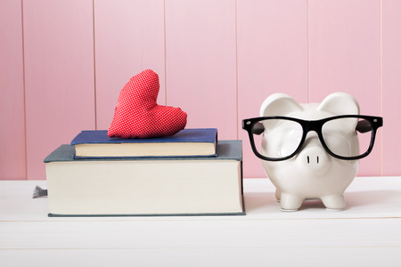 nestegg: Conceptual White Piggy Bank with Eyeglasses Standing Beside Textbooks with Small Red Heart Cushion Against Wooden Pink Wall.