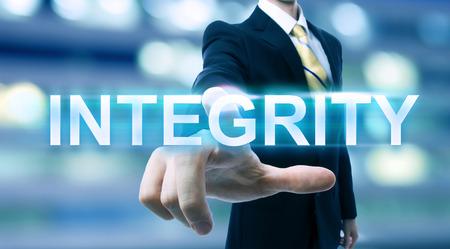 integridad: Empresario apuntando a INTEGRIDAD sobre fondo borrosa ciudad