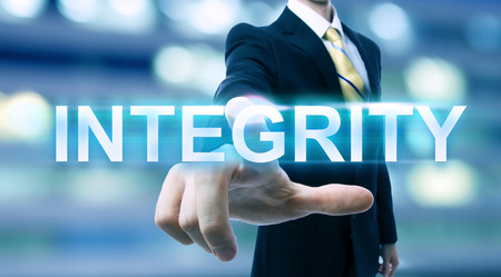 Businessman pointing at INTEGRITY on blurred city background