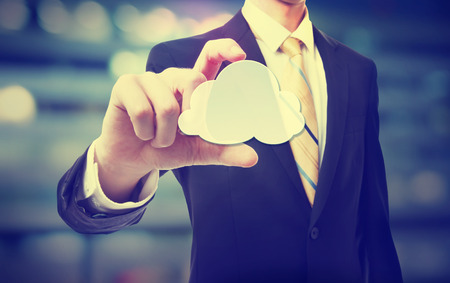 cloud computing technologies: Business man with cloud computing concept on blurred city background Stock Photo