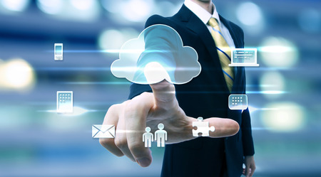 cloud computing: Business man with cloud computing concept on blurred city background Stock Photo