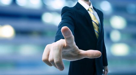 shiny suit: Businessman touching a touch screen on blurred city background Stock Photo
