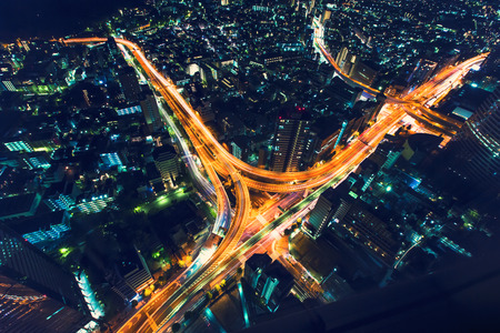 aerial: A massive highway intersection from above at night in Shinjuku, Tokyo, Japan