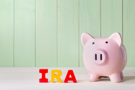 Individual Retirement Account IRA concept with pink piggy bank, wood block letters and green background