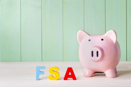 conceito FSA conta de despesas flexíveis com cofrinho rosa, letras de bloco de madeira e fundo verde Imagens