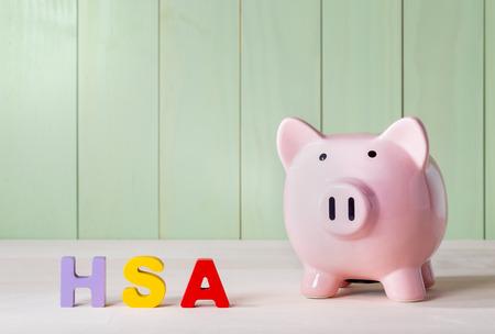 Gezondheid Spaarrekening HSA concept met roze spaarvarken, houten blok letters en groene achtergrond Stockfoto