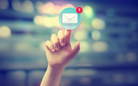 email us: Hand pressing an email icon on blurred cityscape background Stock Photo