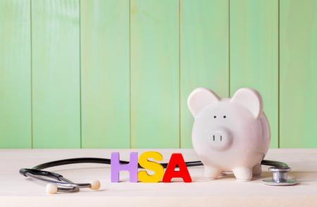 Gezondheid Savingins account HSA concept met wit spaarvarken, hout stethoscoop blokletters en groene achtergrond