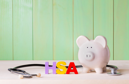 Health Savingins Account HSA concept with white  piggy bank, stethoscope wood block letters and green background Banco de Imagens