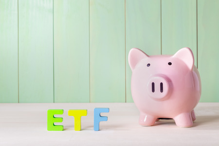 traded: Exchange Traded Funds ETF concept with pink piggy bank, wood block letters and green background
