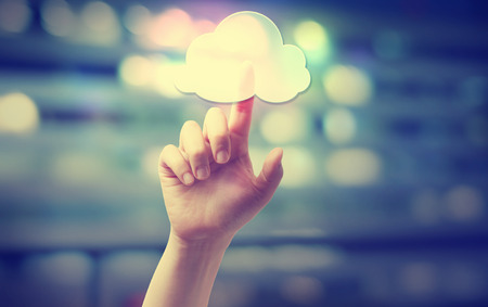 cloud background: Hand pressing a cloud computing icon on blurred cityscape background