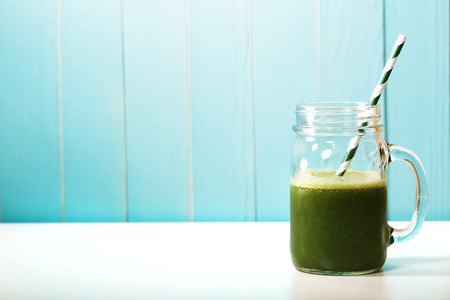 zumo verde: Batido verde en alba�iles frasco con paja de papel en la pared de madera azul