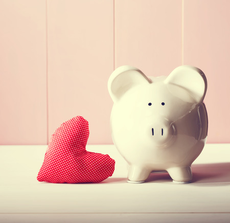 Piggy bank with red heart pillow on pink wooden wall Banco de Imagens