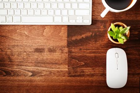 ワイヤレス コンピューターのマウスとキーボード、一杯のコーヒーと観葉植物を頭上から見る木製の机の上にきちんとしたワークステーション