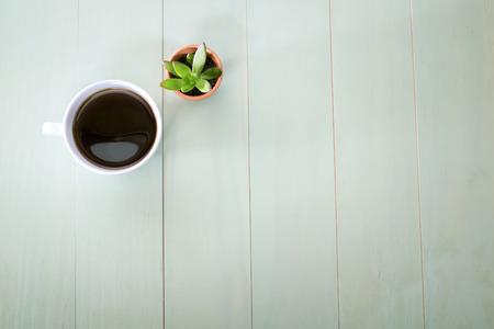 一杯のコーヒーとパステル グリーンの背景に鍋に小さな植物