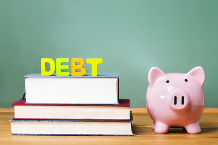 college fund savings: Education debt them with textbooks, piggy bank and chalkboard background