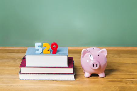 college fund savings: 529 college savings plan theme with textbooks and piggy bank and green chalkboard background