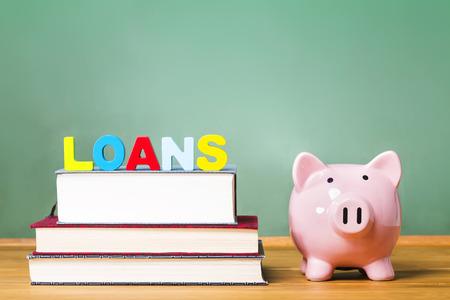 교과서와 돼지 저금통과 녹색 칠판 배경을 가진 학생 대출 테마