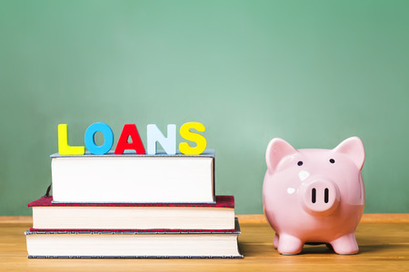 loans: Student loan theme with textbooks and piggy bank and green chalkboard background Stock Photo