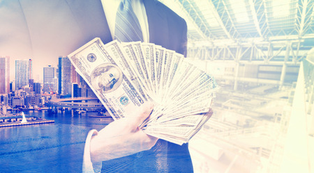 displaying: Double exposure of businessman displaying spread of cash on blurred city background
