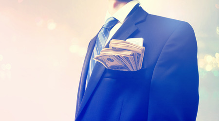 business suit: Businessman with wad of cash on blurred light background