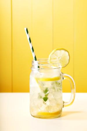 Zelfgemaakte limonade in een stenen pot met grote groene gestreepte stro