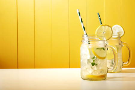 a straw: Homemade lemonade in mason jars with big green paper straw