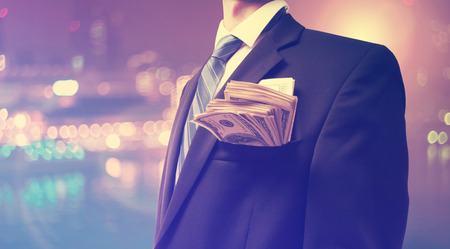 business money: Businessman with wad of cash on blurred city background