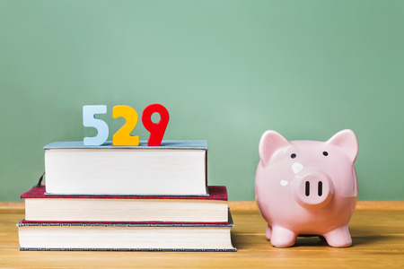 college: 529 college savings plan theme with textbooks and piggy bank and green chalkboard background