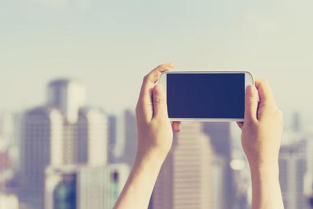 tecnologia: Persona in possesso di uno smartphone fino sopra la città